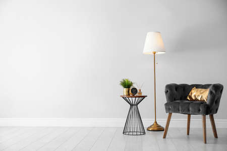 Stylish room interior with comfortable armchair, floor lamp near light wall, space for text Stock Photo