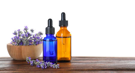 Bottles of essential oil and bowl with lavender on wooden table against white background