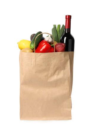Bolsa de papel con verduras frescas y una botella de vino sobre fondo blanco.