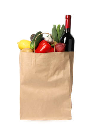 Sac en papier avec des légumes frais et une bouteille de vin sur fond blanc