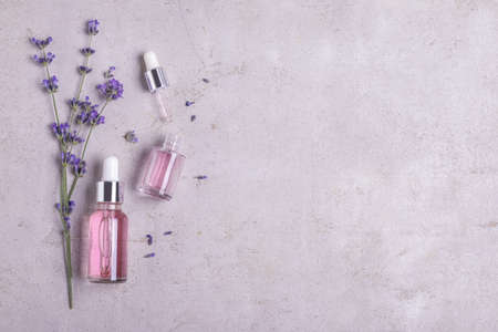 Bottles of essential oil and lavender flowers on stone background, flat lay. Space for text