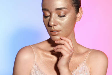 Beautiful young woman with glitter makeup on colorful background