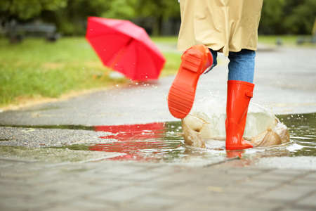 Woman in red rubber boots running after umbrella on street, closeup. Rainy weather Stock Photo