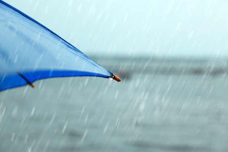 Blue umbrella under rain near river, closeup view