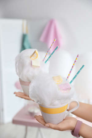 Young woman holding cups with cotton candy dessert on blurred background, closeup. Space for text