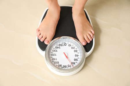 Woman standing on floor scales indoors, above view. Overweight problem Standard-Bild - 129123624