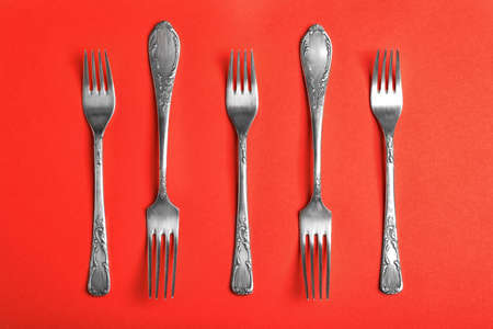 Vintage silver forks on red background, flat lay 스톡 콘텐츠