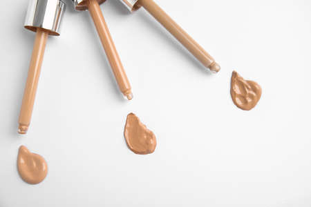 Samples of different foundation shades and droppers on white background, top view