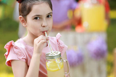 Cute little girl drinking natural lemonade in park, closeup with space for text. Summer refreshing beverage