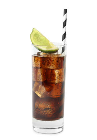 Glass of refreshing soda drink with ice cubes, lime and straw on white background