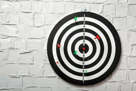 Arrows hitting dart board on white textured wall. Space for text