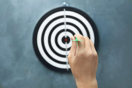 Woman throwing green arrow at dart board on grey background, closeup