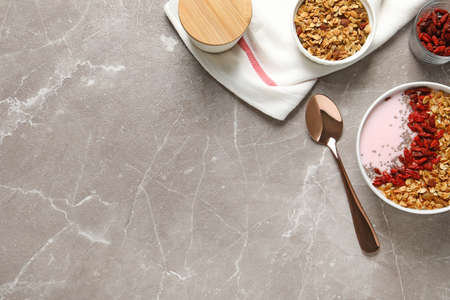 Flat lay composition of smoothie bowl with goji berries on beige marble table