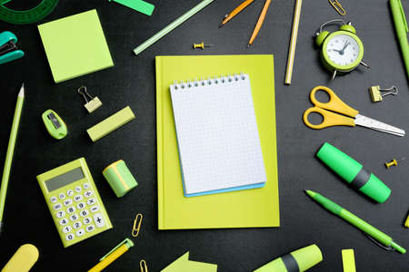 Different bright school stationery and blank notebook on black background, flat lay. Space for text