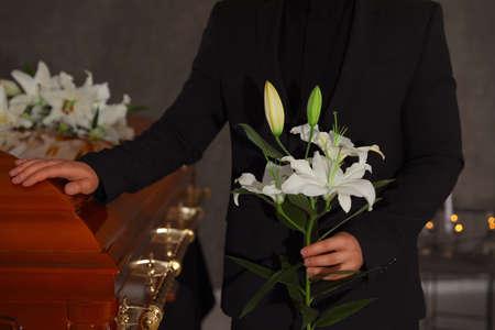 Junger Mann mit weißen Lilien in der Nähe von Sarg im Bestattungsinstitut, Nahaufnahme Standard-Bild
