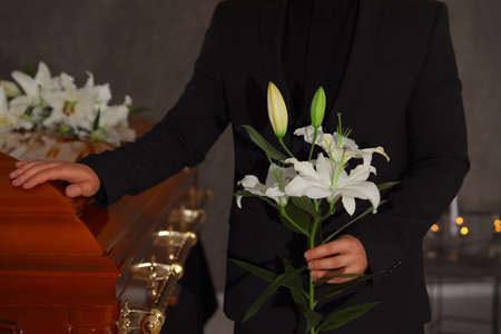 Young man with white lilies near casket in funeral home, closeup
