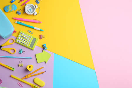 Different bright school stationery on color background, flat lay. Space for text