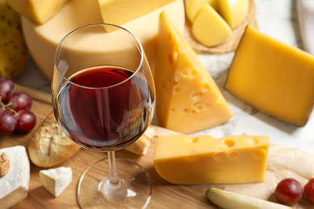 Glass of wine served with delicious cheese and snacks on table, closeup
