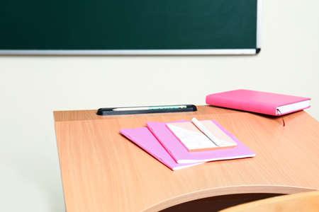 Wooden school desk with stationery near chalkboard in classroom