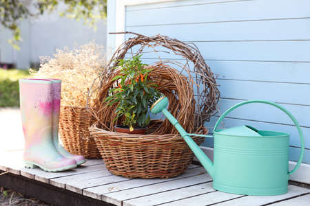Rubber boots, watering can, baskets and plant near house outdoors. Gardening tools Фото со стока