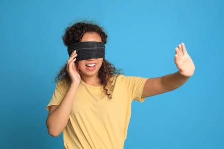 Young African-American woman with black blindfold on blue background Foto de archivo