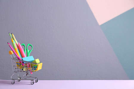 Small shopping cart with different school stationery on color background. Space for text