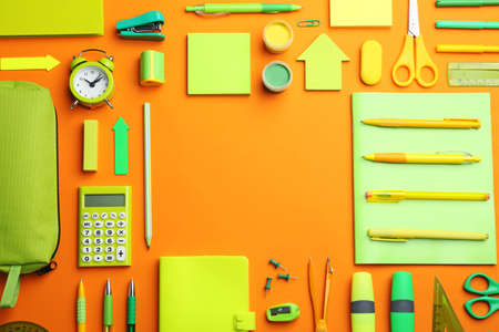 Frame of different bright school stationery on orange background, flat lay. Space for text