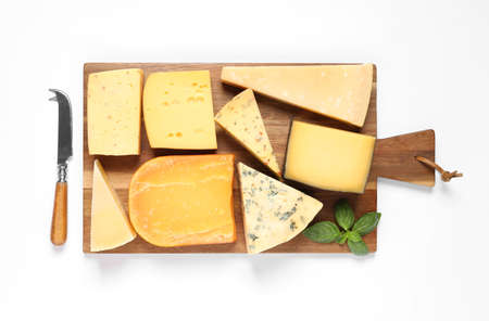 Wooden board with different kinds of cheese, basil and knife on white background, top view