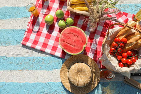 Straw hat and different products for summer picnic on checkered blanket, flat lay