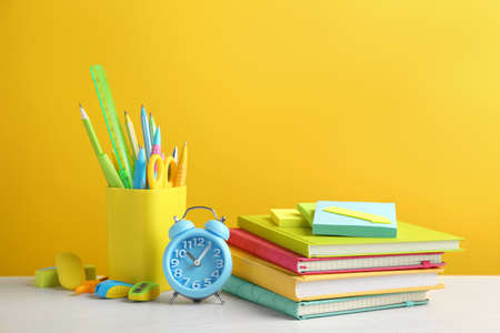 Different school stationery on white wooden table against yellow background Stock fotó