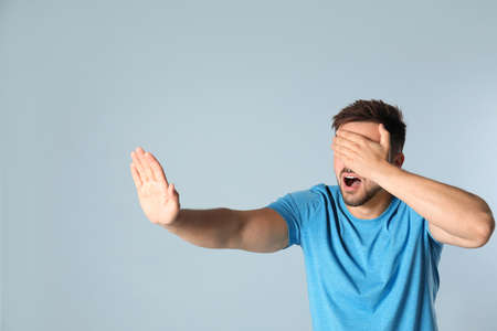 Young man being blinded on grey background
