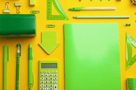 Green school stationery on yellow background, flat lay Stock fotó