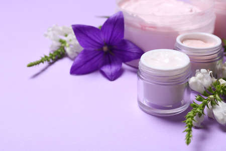 Jars of body cream and flowers on lilac background. Space for text