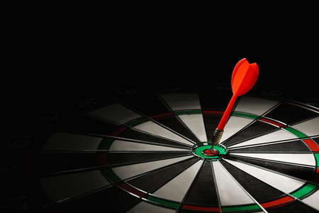 Red arrow hitting target on dart board against black background. Space for text