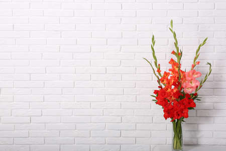 Vase with beautiful gladiolus flowers on table against white brick wall. Space for text