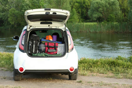 Car with camping equipment in trunk on riverbank. Space for text
