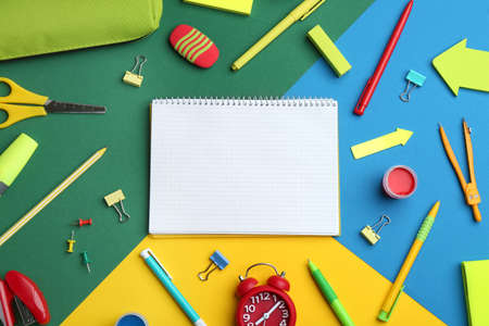 Different bright school stationery and blank notebook on color background, flat lay. Space for text