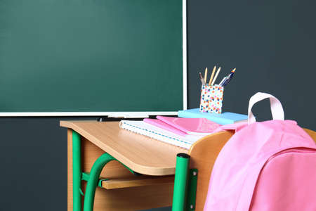 Wooden school desk with stationery and backpack near blackboard on grey wall