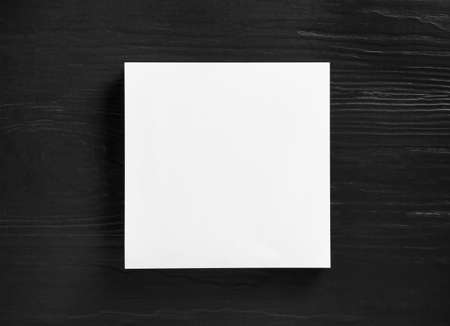 Stack of blank paper sheets for brochure on black wooden background, top view. Mock up