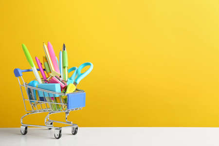 Small shopping cart with different school stationery on white wooden table against yellow background. Space for text