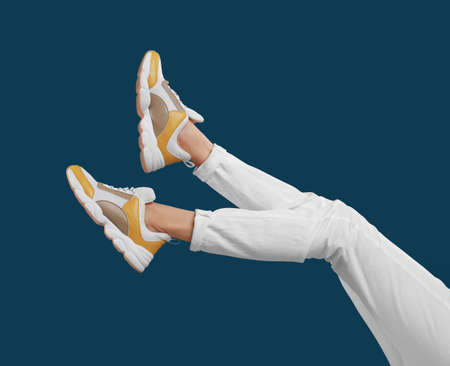 Woman in stylish sport shoes on blue background
