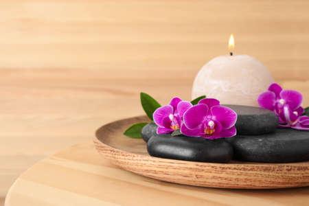 Plateau avec pierres de spa, fleurs d'orchidées et bougie sur table en bois. Espace pour le texte