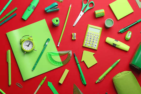 Green school stationery on red background, flat lay Stock fotó