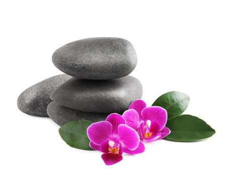 Pile of spa stones and orchid flowers on white background