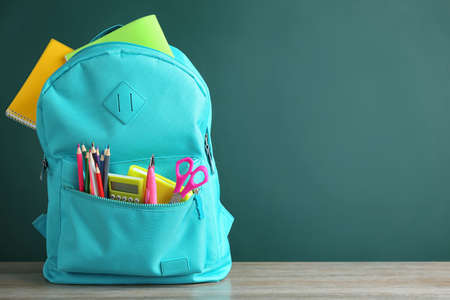 Bright backpack with different school stationery on wooden table near green chalkboard. Space for text
