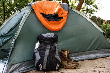 Camping tent with sleeping bag, boots and backpack on beach