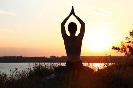 Young woman practicing yoga outdoors on sunset. Zen meditation Zdjęcie Seryjne