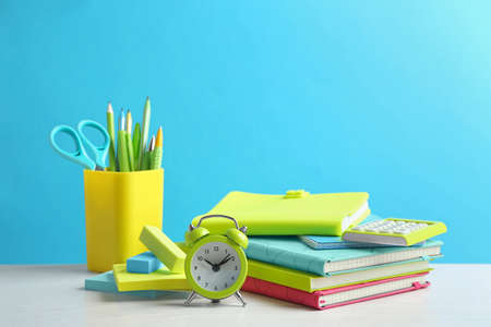 Different school stationery on white table against light blue background