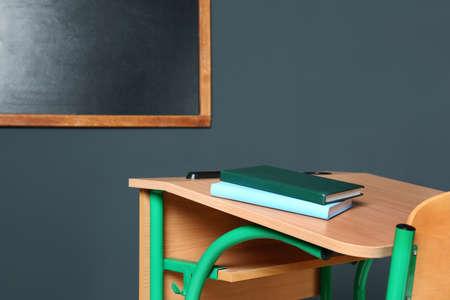 Wooden school desk with stationery near blackboard on grey wall