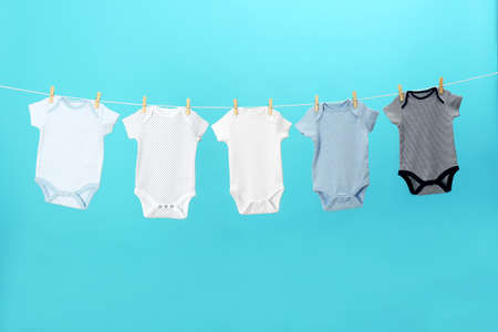 Colorful baby clothes hanging on clothes line against blue background. Laundry day